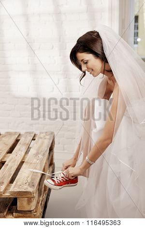 Pretty bride in wedding gown getting on sneakers. Side view.