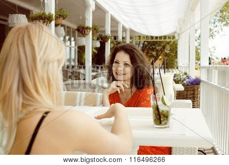 portrait of two pretty friends in cafe interior drinking and talking
