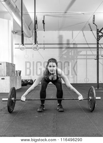 Young Woman Lifting A Barbell At A Gym