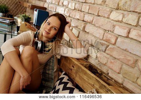 Attractive young woman sitting at home, relaxing.