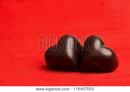 Two Candies In A Shape Of A Heart On Red