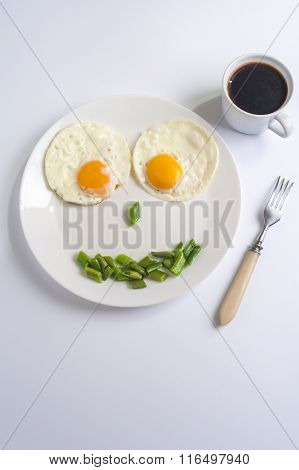 Two fried eggs with green beans on white plate fork and cup of coffee on light background. English b