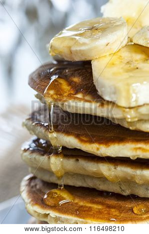 Stack of homemade pancakes with banana slices and honey, close up.