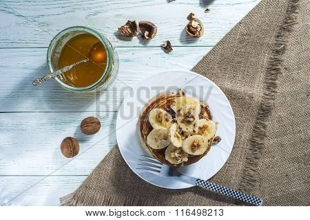 Homemade pancakes with banana slices, honey and walnuts on wooden background.