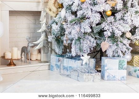 Brightly lit christmas tree with lots of gifts