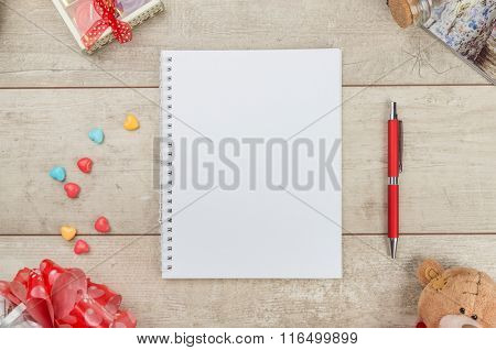 Notepad, pen, candy and teddybear on wooden table