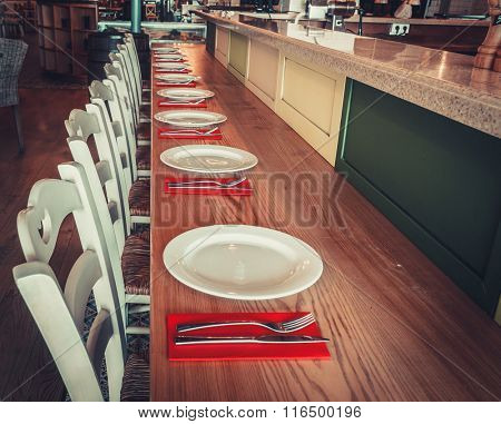 Interior of modern restaurant with table, chairs and tableware
