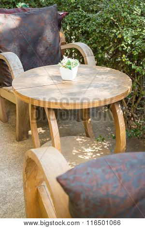 Table And Chairs Standing In The Garden With Shadows