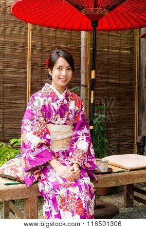 Japanese womanwearing kimono and sitting at tea house