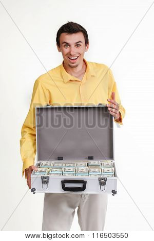 Young businessman with suitcase full of money.