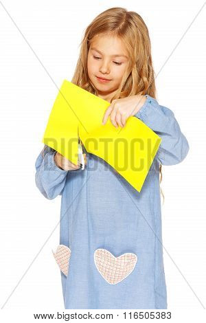 Cute little girl with scissors and yellow paper