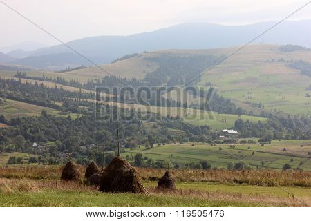 Mountain highland view with the haystacks in summer