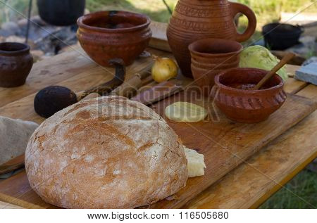 Ancient Wooden And Clay Dishes With Bread On A Table