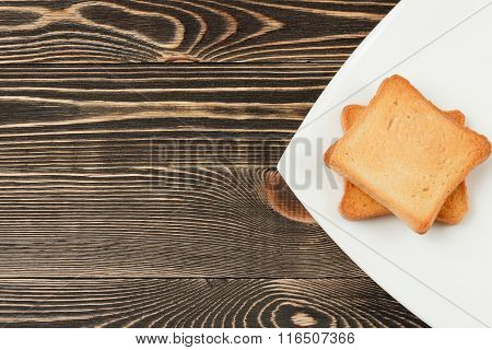 Toast bread in a white plate on wooden background.