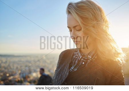 Close up of beautiful woman standing on a viewpoint against sky and sundown in warm spring evening
