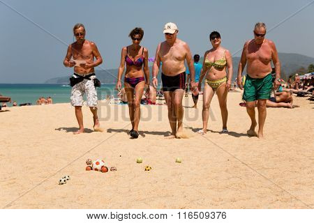 KARON BEACH, THAILAND - CIRCA FEBRUARY, 2015: European tourists are playing the French game boules (petanque). Karon beach is one of the most popular beaches among tourists in Phuket