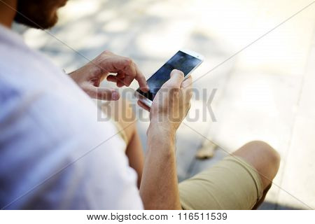 Hipster guy searching information on cell telephone while sitting outdoors