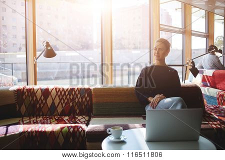 Thoughtful female waiting for a friends while sitting front open laptop computer in coffee shop