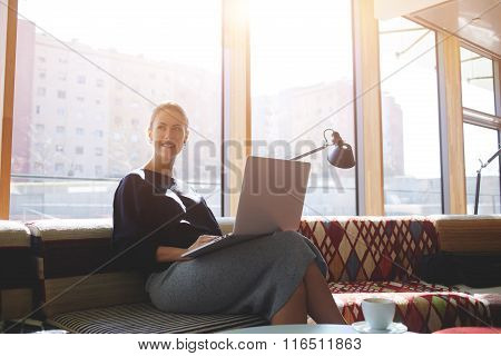 Cheerful female dreaming while sitting with laptop computer in modern cafe