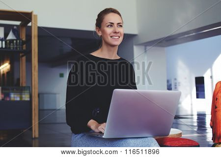 Happy woman dreaming about something while waiting until downloads the file on laptop computer