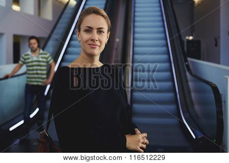Elegant woman entrepreneur posing near escalator in airport while waiting for airplane