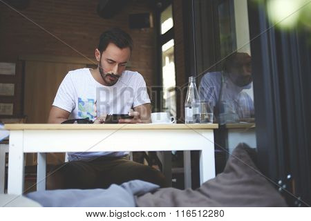 Successful male watching video on digital tablet while waiting for order in luxury cafe