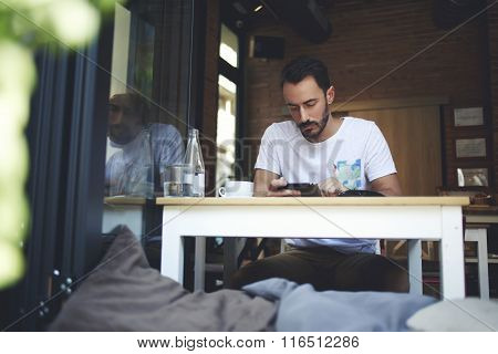Male concentrated reading world news on digital tablet during work break in restaurant