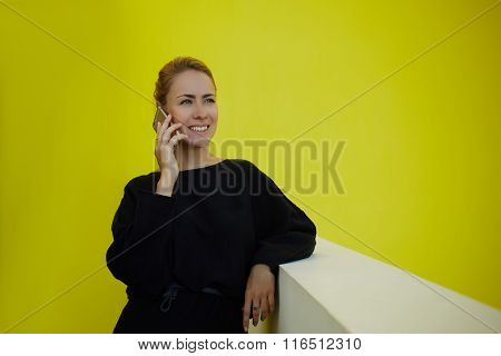 Smiling female lawyer talking on mobile phone after winning court case while standing in office