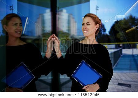 Woman administrator holding touch pad and smiling to new clients of the hotel which she waiting