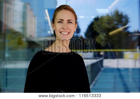 Half length portrait of happy and successful female hostess of modern hotel posing outside