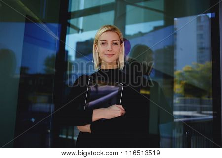 Young attractive female hostess of hotel holding digital tablet while resting in work break outside