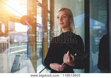 Young elegant woman thinking something while standing with touch pad near office window outside