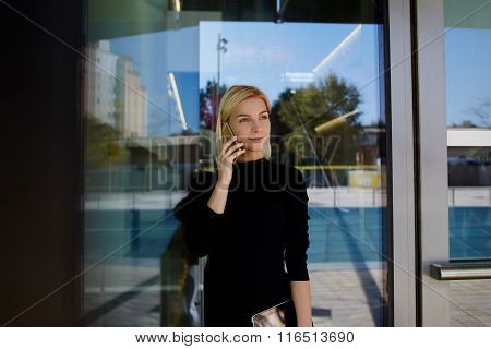Elegant female employer phoning with cell telephone during work break outside company's building