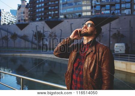 Stylish young man talking on mobile phone and looking up while standing in urban scene