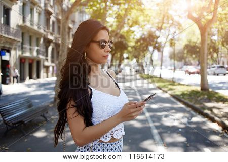 Gorgeous Hispanic woman chatting on mobile phone while standing in the street in summer day