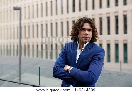 Half length portrait of handsome businessman standing with crossed arms outdoors during work break