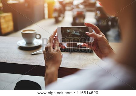 Close up of women's hands photographing sweet dessert on mobile phone for social network picture