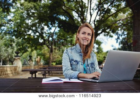 Smiling woman enjoying good day while preparing coursework on laptop computer