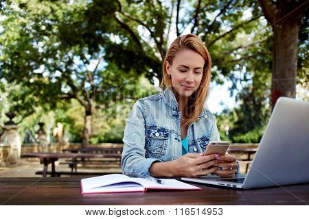 Beautiful woman chatting on mobile phone while sitting with portable laptop computer on campus