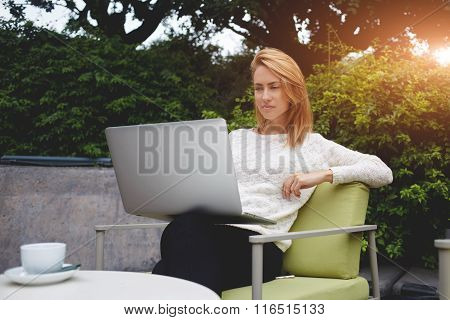 Beautiful female reading fashion news on net-book while sitting in restaurant outdoors
