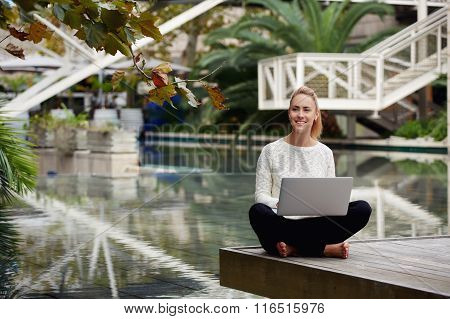Beautiful young woman smiling to someone during work on laptop computer outside in autumn park