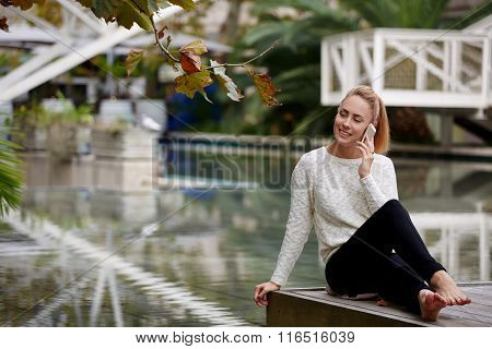 Charming woman talking on cell telephone while sitting on a wooden pier in warm autumn day