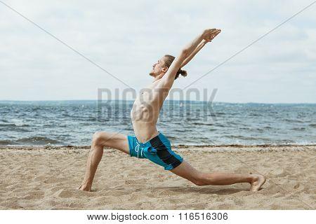 Adult thin man with naked torso doing yoga on the beach. Virabhadrasana pose