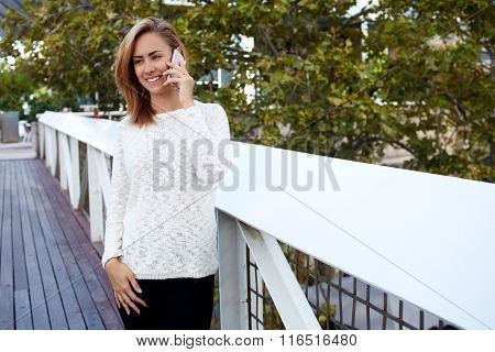 Cheerful pretty woman calling with smart phone while standing outdoors on bridge near her house