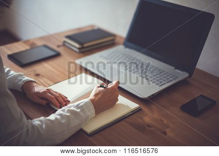 Woman freelancer female hands with pen writing on notebook at home or office.