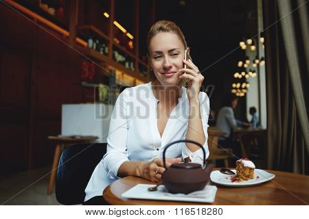 Beautiful European woman calling with her mobile phone while relaxing in cafe during coffee break