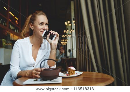Beautiful female dreaming about something good while waiting for a call on cell telephone