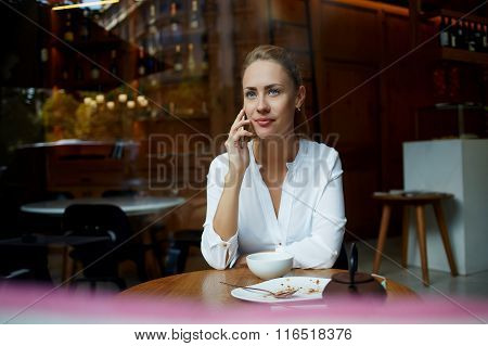Charming female phoning via cell telephone while waiting for friends in comfortable cafe