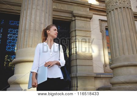 Beautiful female tutor standing with laptop computer near University before starts lesson