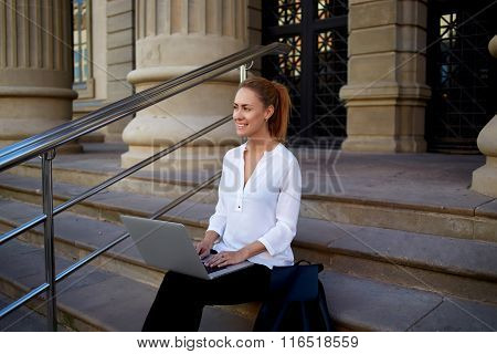 Young female student with beautiful smile sitting with open laptop computer on the stairs